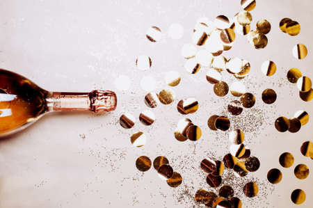 Bottle of champagne with golden confetti and glitter