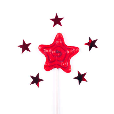Red star shaped lollipop on white background with five stars confetti. Stock fotó