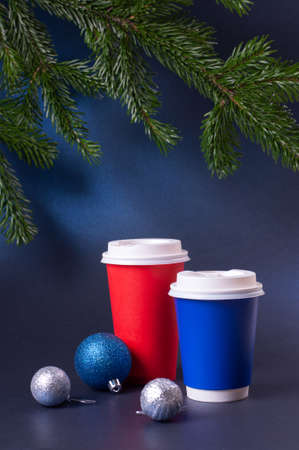 Blank blue and red to go coffee cups and pine tree branches on trendy classic blue background. Stock fotó