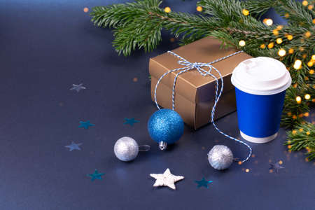 Blank blue takeaway coffee cup with Christmas decorations and confetti. Golden gift box near pine tree branches.
