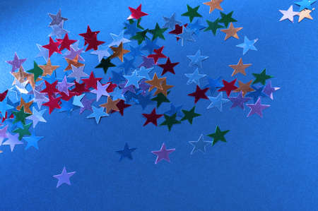 Festive colorful stars trendy blue background. Christmas abstract flat-lay.