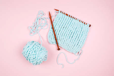Mentol yarn ball and wodden knitting needle on light pink background