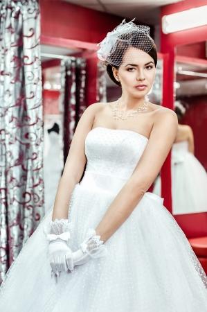 checkroom: Beautiful bride in white dress in checkroom Stock Photo