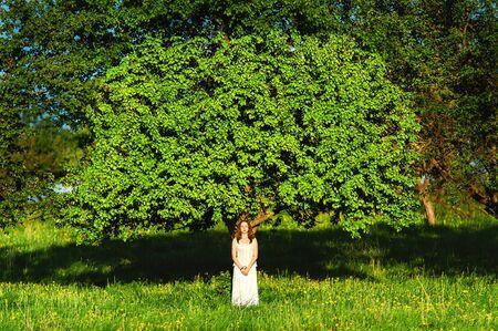 pensiveness: La donna in abiti bianchi vicino a un albero