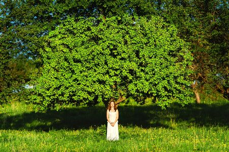 pensiveness: The woman in white clothes near a tree