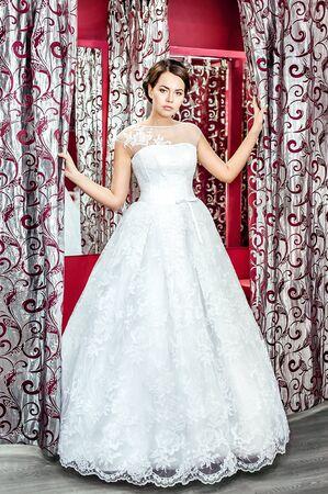 checkroom: Beautiful bride in long white dress in checkroom