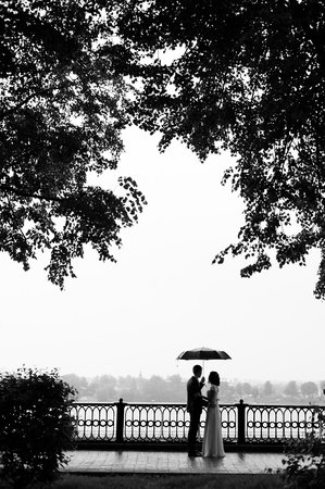 love in rain: silhouette young loving couple with an umbrella under trees
