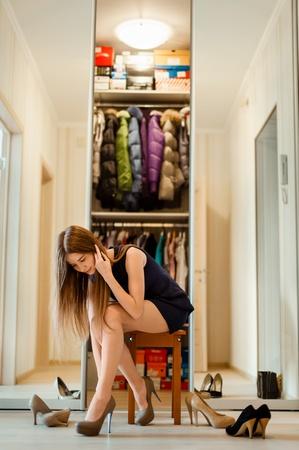 closet: beautiful girl with long hair chooses high heel shoes
