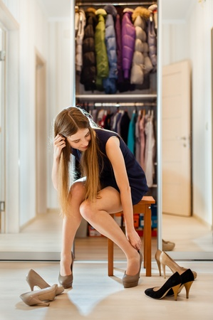 beautiful young woman with long hair  trying different kinds of shoes photo