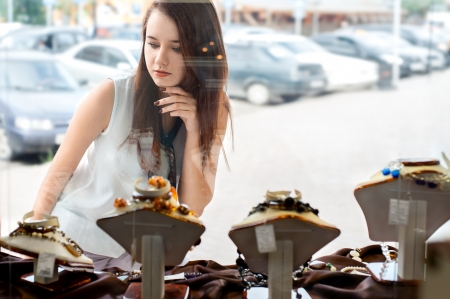 young woman with long dark hair selects a piece of jewellery in the shop window photo