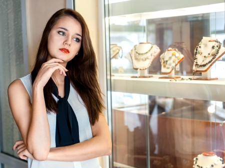 jewelry store: beautiful girl with long dark hair  chooses jewellery in the shop window