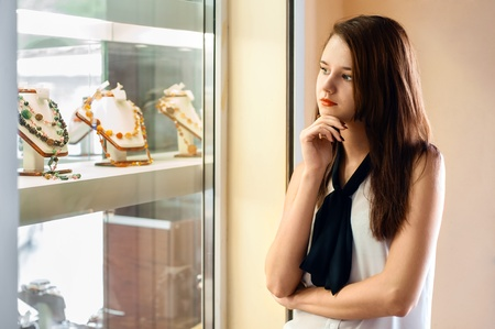 young woman with long dark hair chooses jewellery in the shop window photo