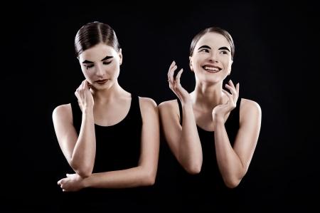 mimo: hermanas gemelas - mimos tristes y divertidas sobre fondo negro Foto de archivo