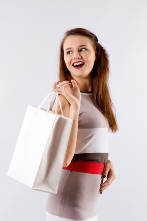 Young brunette girl in dress with shopping bag on a white background photo
