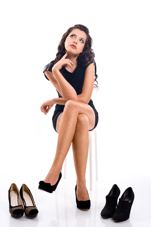 beautiful brunette girl with long hair chooses shoes  isolated on white background photo