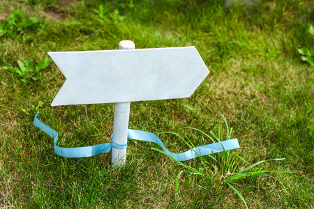 empty wooden  arrow sign on the green grass photo