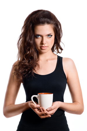 beautiful young woman with dark wavy hair looking into the camera, holding cup of coffee or tea in her hand. Isolated on white background. 版權商用圖片