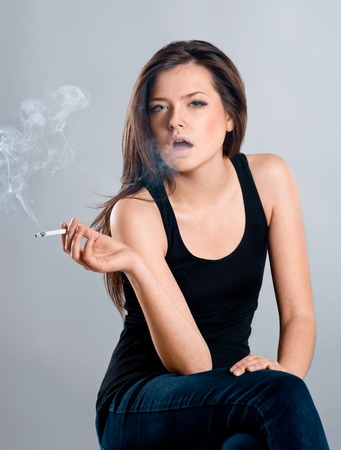smoking girl: Attractive  brunette woman  smoking a cigarette, blowing smoke