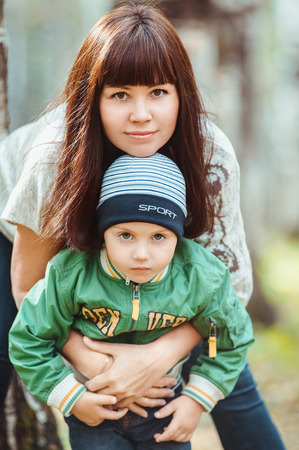 cute baby boy hug his lovely mom in autumn park, photo