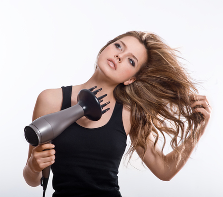 Brunette girl dry with hairdryer their long hair,  isolated on white background Stock Photo - 22842954