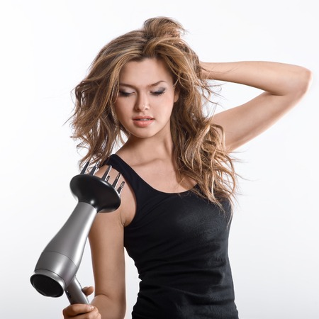 attractive girl blows dry her hair with hairdryer,  isolated on white background Stock Photo - 22842960