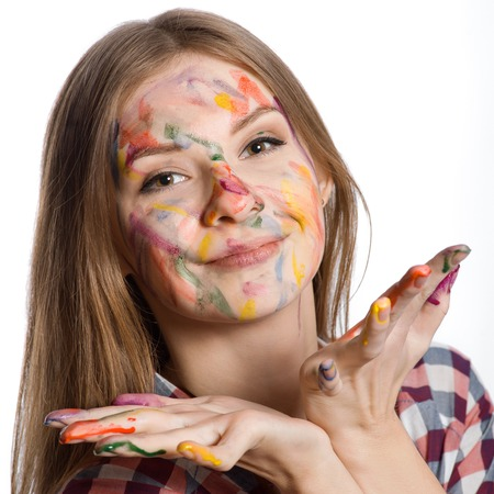 smiling girl with painted face and hands in colorful paints, isolated on white photo