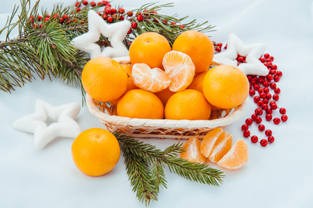 new year composition in basket with mandarins and fir tree photo