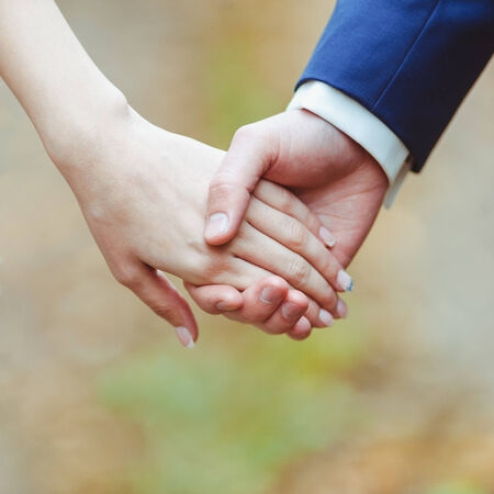 Close-up image of a young loving couple holding hands photo
