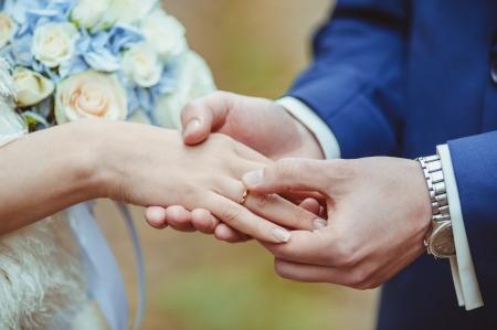 Bruidegom hand om een trouwring aan de vinger van de bruid