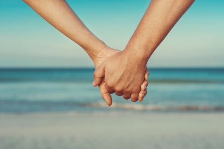 Man and woman holding by hands against the sea photo