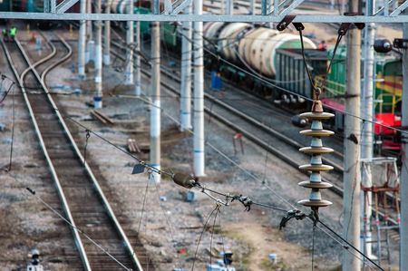 the insulator: High-voltage electrical insulator electric line at railway station Stock Photo