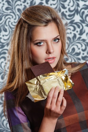 starvation: portrait of beautiful woman eating bar of chocolate