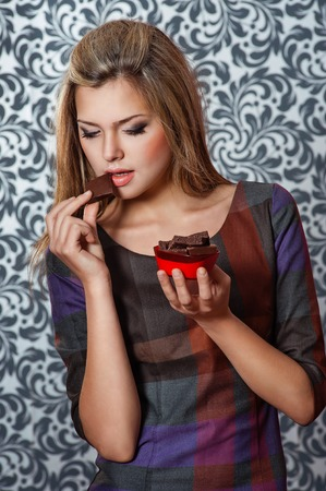 portrait of charming woman eating chocolate pieces photo