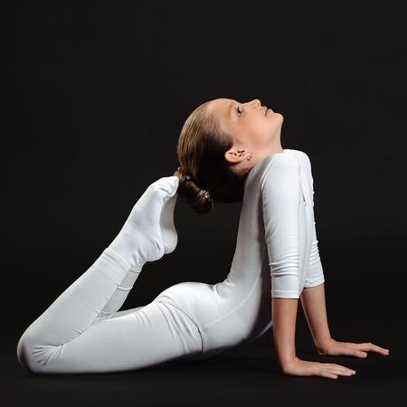 young girl doing gymnastics over black background