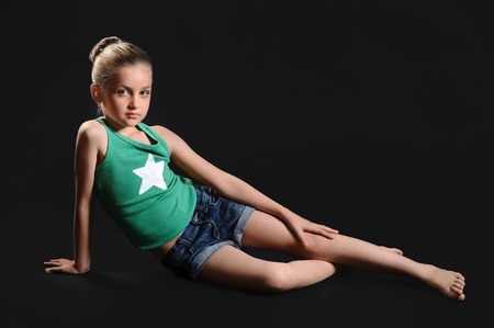 beautiful girl sitting on the floor over dark background photo