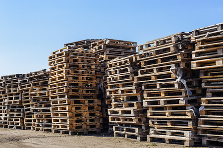stacked up: Stacked up colorful wooden cargo pallets against a blue sky