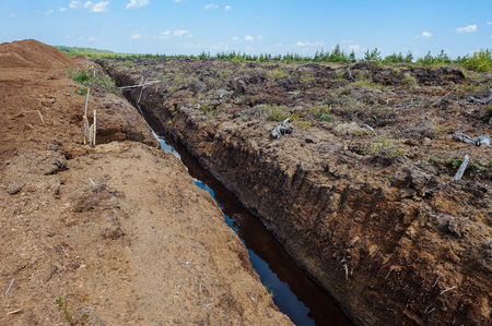 Peat extraction. Reclamation ditch dug in the fields. Agricultural technology. Stock Photo