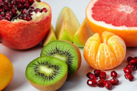 Set of sliced fruits: kiwi, mandarin, pomegranate, grapefruit, apple