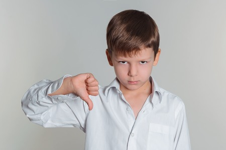 Portrait of sad boy in white shirt showing thumbs down sign photo