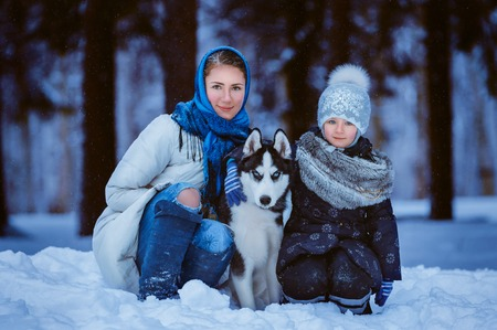 mother and young daughter walking with husky dog, winter time photo