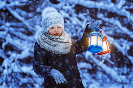 torchlight: little girl holding in her hands two luminous Christmas flashlight,  winter time Stock Photo