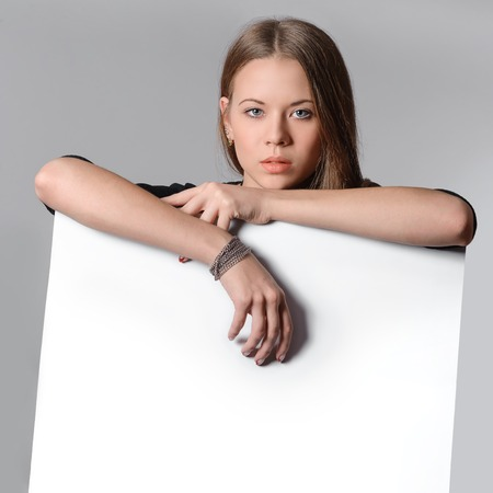 beautiful young woman presents with a blank white board photo