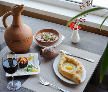 serving table, traditional dish of georgian cuisine, khachapuri, a soup, a jug of wine