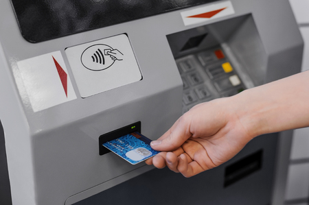 withdraw: Hand inserting credit card into bank machine to withdraw money