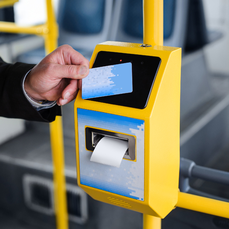 fare: Human hand holding plastic cards. Passenger pays for the fare in public transport. Payment terminal, credit card reader, sales concept.