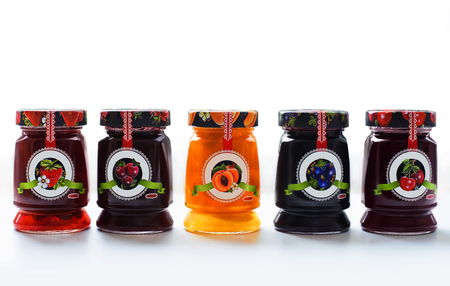 fayre: jars of delicious berry jam on white background