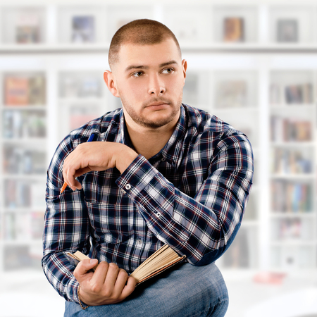undergrad: student wearing checkered shirt with a book in library