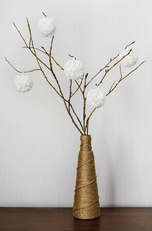 Vase with dry branches adorned with white balls on a wooden table. Handmade. The idea for  home decoration