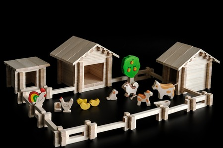 barnyard: a small wooden house, building kit, toy farm and barnyard on a black background