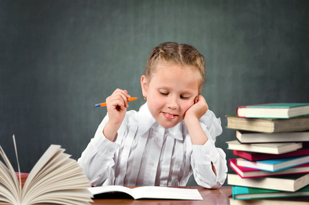 primary education: Young schoolgirl sitting at a desk in the classroom. Primary education Stock Photo